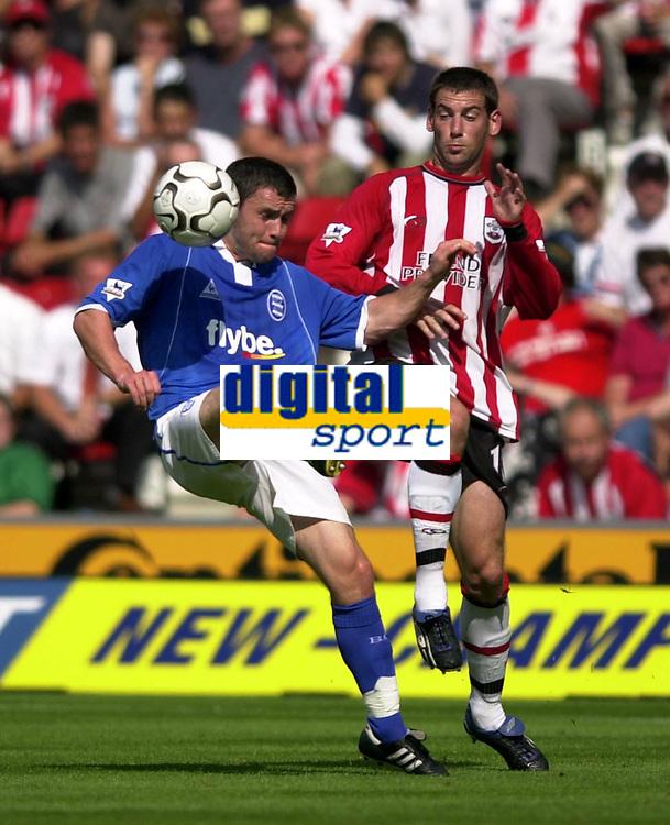 Fotball<br /> Premier League England<br /> 23.08.2003<br /> Foto: Digitalsport<br /> Norway Only<br /> <br /> Photo: Richard Lane.<br />Southampton v Birmingham City. Barclaycard Premiership.<br />23/08/2003.<br />Danien Johnson gets the ball away as Rory Delap challenges.