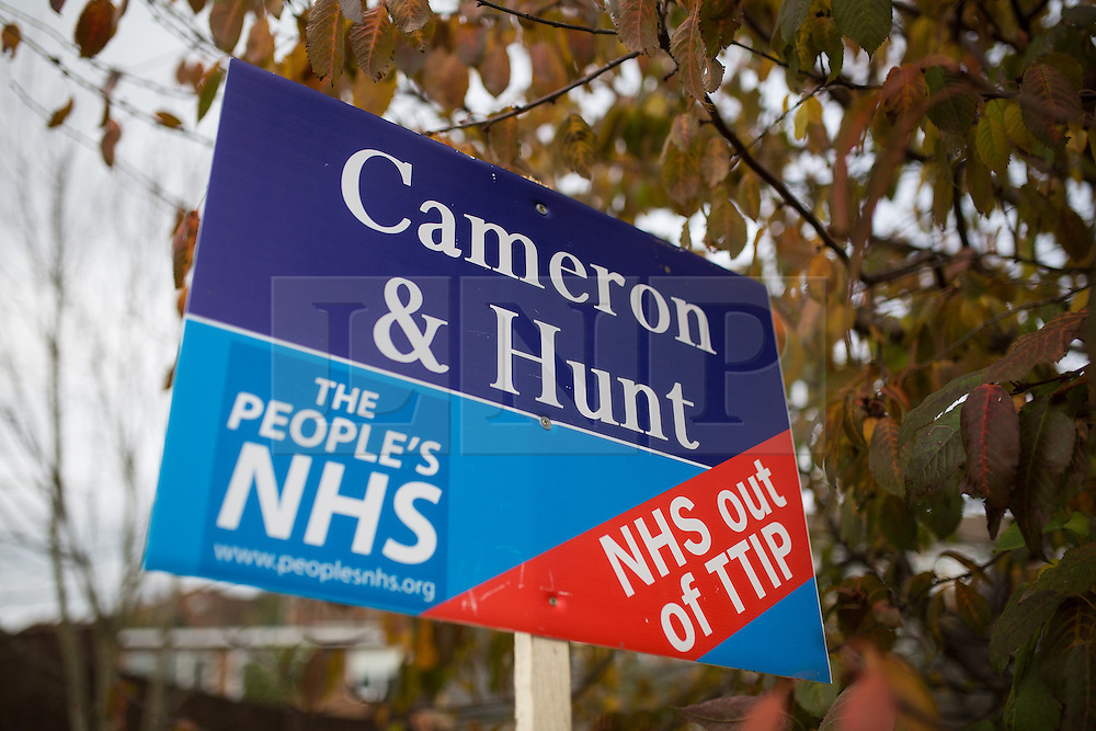 """© Licensed to London News Pictures . 17/11/2014 . Kent , UK . Mock estate agent board calling for """" NHS out of TTIP """" and referencing Prime Minister David Cameron and Health Secretery Jeremy Hunt , outside a house in Strood . Photo credit : Joel Goodman/LNP"""