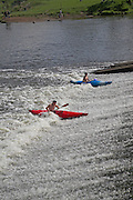 Canoeing in white water from the weir on the River Avon in the Vale of Evesham, Fladbury, Worcestershire, Englandd