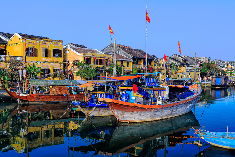 Hoi An Riverside: An aquatic view of down town Hoi An riverside, with the characteristic colonial styled yellow buildings and the boats at harbour, Hoi An Vietnam.