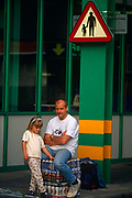 A father and daughter wait for the man's wife to return with their car after the family have returned from a booze-cruise from Dover to Calais. Back in England, the dad sits on crates of Fosters, John Smiths and Stella Artois lagers purchased in a French supermarket, considerably cheaper in Euros, than in Pounds. Waiting patiently with their merchandise, the two sit and stand beneath a road traffic sign telling adult pedestrians to hold on to their children as Dover is a busy sea port, where heavy trucks and fast-moving vehicles make it dangerous for the young. Booze cruises are popular ways of stocking parties inexpensively though with exchange rates fluctuating to make the Euro's value against the British Pound, the booze cruise market slowed.