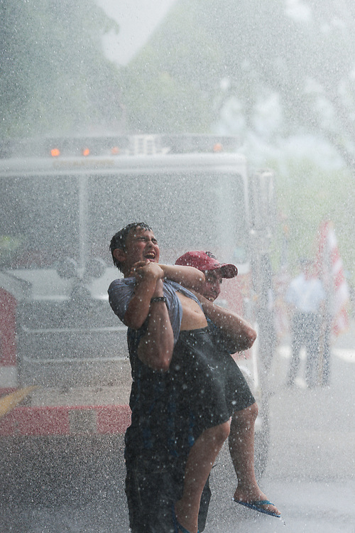 Nino Dushi holds up his cousin Alexander Silaz in a fountain of water produced from a firetruck hose at the end of the route of the annual memorial day parade in Washington on May 30, 2016.