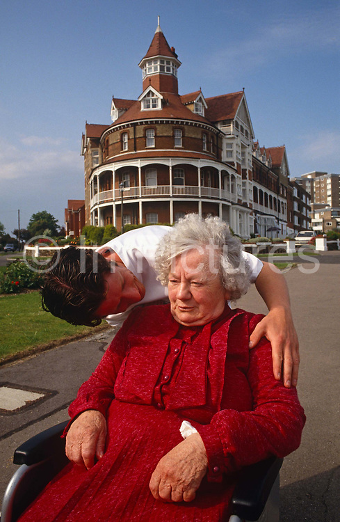 A carer from an elderly peoples' residential home bends down to speak to an old lady who has been taken out for her daily walk in the fresh-air. The lady however cannot walk but seems to be enjoying her daily constitutional from the comfort of her wheelchair that the nursing specialist kindly pushes along a promenade in Frinton-on-Sea in Essex. With her hankie tucked in her sleeve she also seems to be slightly confused as if she might be suffering from a dementia or possibly just old and tired from the hardships after Britain at war. By 2050 the percentage of people worldwide over 65 years will have doubled.