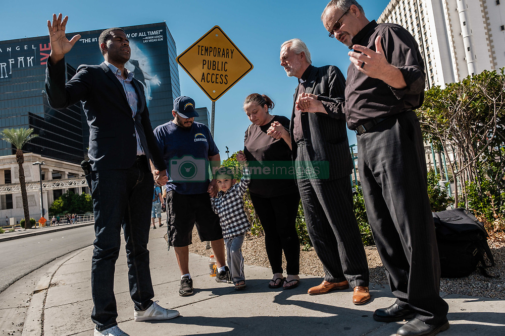 October 3, 2017 - Las Vegas, Nevada, U.S - Pastor DIMAS SALABERRIOS (left) from New York,  Pastor BILL DEVIN (Center right) from New York and JIM MARTSOLF (right) pray with passersby on Las Vegas Boulevard near the Mandalay Hotel and the site of Sunday's mass shooting which claimed the lives of 59 people and injured hundreds of others.  Salaberrios's sister was at the Music Festival Sunday night when the shooting started but was not injured. (Credit Image: © Nick Otto via ZUMA Wire)