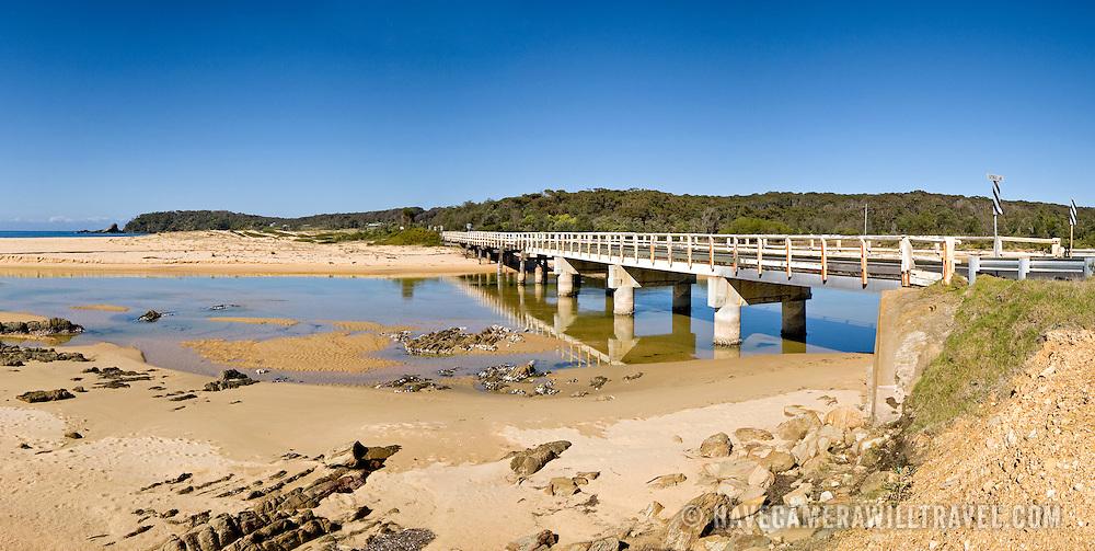 Beach on southern NSW coast with bridge.