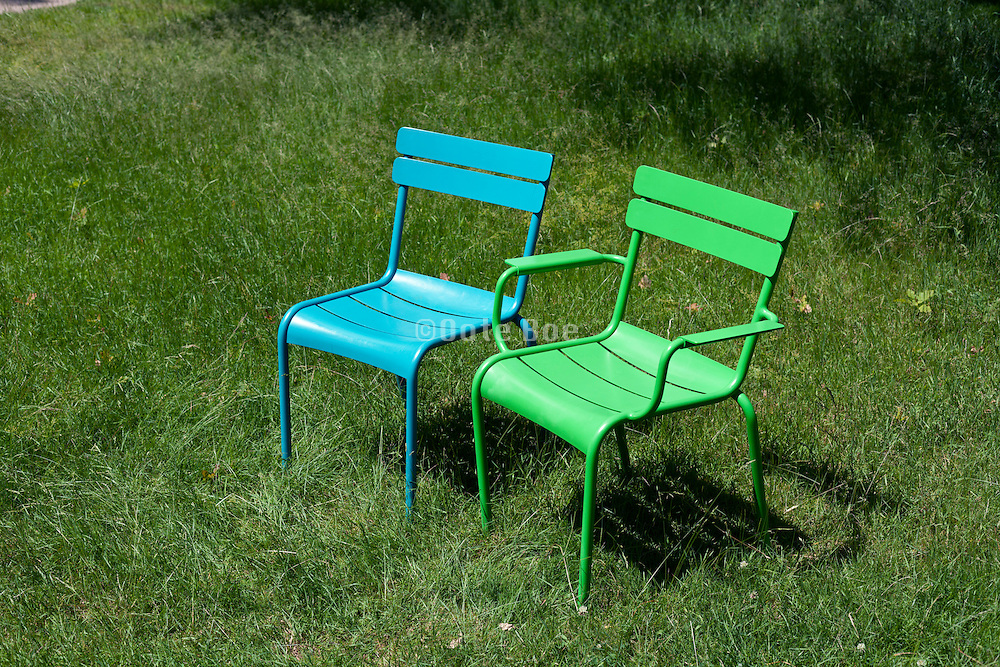 green and blue outdoors chairs standing in a grass field