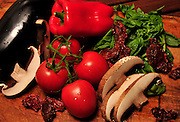 Portabella mushrooms, vine-ripened tomatoes, fresh basil, eggplant and sun dried tomatoes on a cutting board.