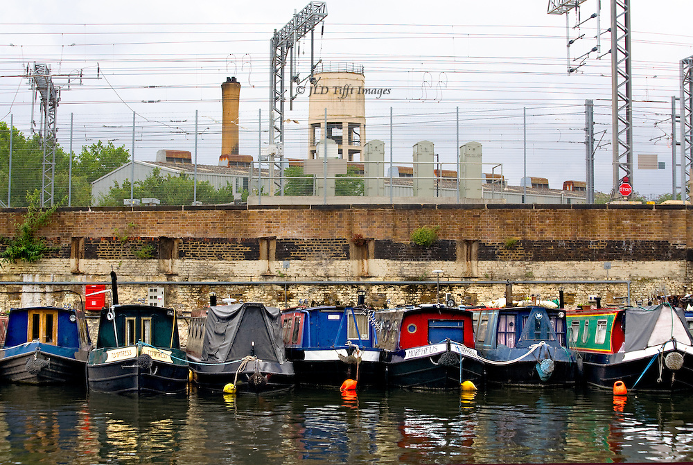London, Regent's Canal : seven barges tied up in a row at a wall designated for that purpose near Islington.  Cabins are painted bright primary colors.  Four orange and yellow buoys float alongside four prows.  Behind, railway tracks and overhead wires, water tower, industrial chimneys.