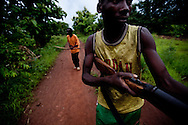 """Members of the """"arrow boys"""" a vigiante group formed in Western Equatorial State in Sudan to protect villagers from the LRA attacks patrol on May 22, 2010. Members of this group traded gunshoot with the LRA earlier in the day. The LRA has attacked a number of roads, villages, and clinics in the area over the last week pushing thousands of people to flee to larger towns for protection."""