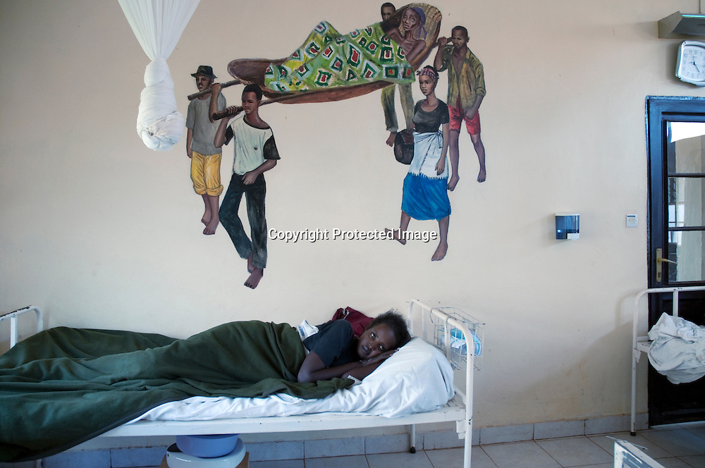 """A patient in the female ward of the rebuilt Rwinkwavu hospital in southeast Rwanda. The hospital is run by the Rwandan Minstry of Health and Boston based Partners in Health. Partners in Health, co-founded by Dr. Paul Farmer, has 888 paid community health workers called """"accompagnateurs"""" attached to the hospital. They visit pateints at home to administer drugs for chronic dieases such as TB and HIV/Aids. The accompagnateurs program in Rwainkwavu builds upon Rwanda's system of 30,000 elected volunteer Community Health Wokers.  The Clinton Foundation is a major project donor."""