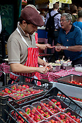 Stall holder prepares Strawberries and Cream. Borough Market is a thriving Farmers market near London Bridge. Saturday is the busiest day.