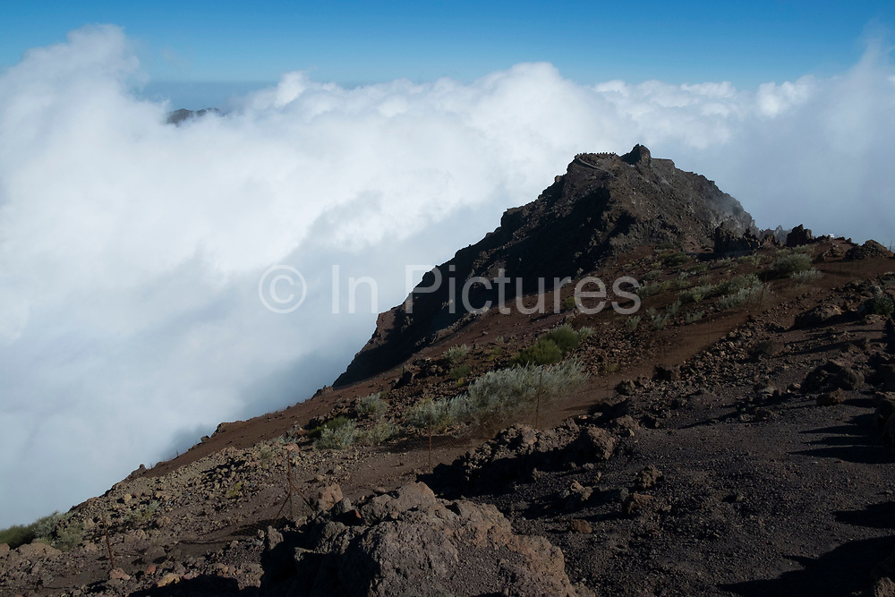 View from the Roque de los Muchachos looking south to the Caldera de Taburiente National Park in La Palma, Canary Islands, Spain. La Palma, also San Miguel de La Palma, is the most north-westerly Canary Island in Spain. La Palma has an area of 706km2 making it the fifth largest of the seven main Canary Islands. Caldera de Taburiente National Park Spanish: Parque Nacional de la Caldera de Taburiente is a national park on the island of La Palma, Canary Islands, Spain. It contains the enormous expanse of the Caldera de Taburiente, once believed to be a huge crater, but nowadays known to be a mountain arch with a curious crater shape, which dominates the northern part of the island. It was designated as a national park in 1954. The caldera is about 10km across, and in places the walls tower 2000 m over the caldera floor. The highest point is the Roque de los Muchachos on the northern wall, at 2426 m altitude, which can be reached by road.