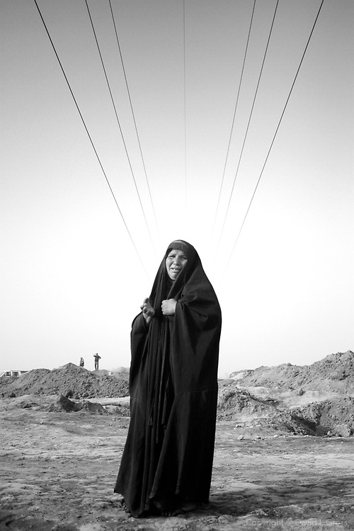 Wailing women in black dot the mass grave at Hillah, Iraq, where over 2,000 bodies have been exhumed.