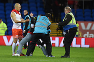 A 'fan' is held back as he tries to get to Arjen Robben of Netherlands as he walks off the field at the end of the match.  Vauxhall International football friendly, Wales v The Netherlands at the Cardiff city stadium in Cardiff, South Wales on Friday 13th November 2015. pic by Andrew Orchard, Andrew Orchard sports photography.