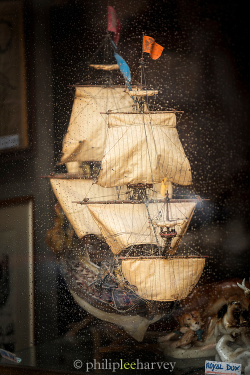 Close-up of model of ship in antique shop window, Trieste, Italy