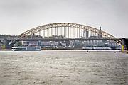 Nederland, Nijmegen, Waal, 21-10-2018 Waalbrug bij Nijmegen bij extreem laagwater in de Waal en Rijn. Zicht op de stad terwijl een passagiersschip er onderdoor vaart. De oude brug zal binnenkort een grondige renovatie ondergaan die lang uitgesteld is vanwege de vondst van giftige verf met chroom6 component op het staal.Foto: Flip Franssen