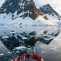 Guests on the bow of the National Geographic Explorer observe the stunning landscape as the ship passes through the Lemaire Channel in Antarctica.