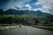 Vietnamese men cross a bridge on their bike, Muong La District, Son La Province, Vietnam, Southeast Asia