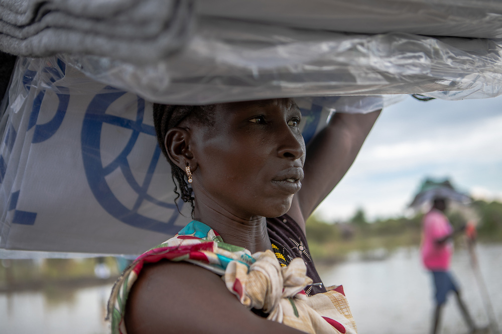 A woman carries a load of non-food items, such as blankets and tarpaulin, distributed by NGOS, following devestating flooding, in Pibor, Boma State, South Sudan, on 6 November 2019 // Photo credit: UNICEF South Sudan/de la Guardia
