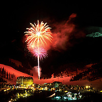 Fireworks display over the base lodge at Big Sky, Montana.  Pioneer Mt. (site of Yellowstone Club) lit up in background.