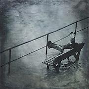 Boy sitting on a bench amidst a flooded promenade.