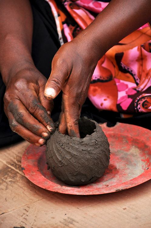 A member of Mashamba Village pottery begins shaping a small traditional Venda pot. The plate is used to quickly turn the pot, keeping the shape round and even. Limpopo, South Africa