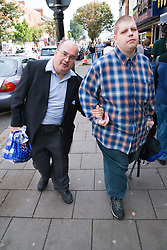 Man helping his friend who has a disability to walk along the street whilst on a day trip to Skegness organised by Nottingham Disabled Friendship Club,