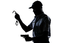 An afro American policeman holding handcuffs and handgun in studio on white isolated background