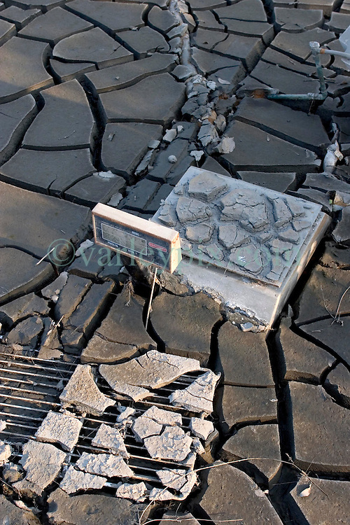 30 Sept, 2005.  New Orleans, Louisiana. Lower 9th ward. Hurricane Katrina aftermath. <br /> The remnants of the lives of ordinary folks, now covered in mud as the flood waters recede. A cash register lies stuck in the mud. <br /> Photo; ©Charlie Varley/varleypix.com