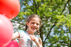 Portrait of a smiling girl holding red balloons, Munich, Bavaria, Germany