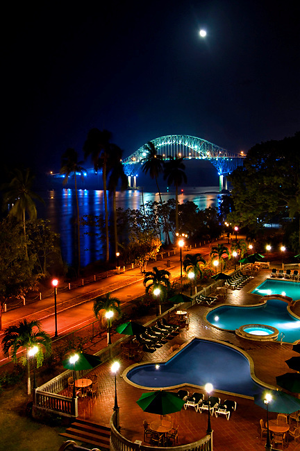 The night moon rises over the Bridge Of The Americas, the Pacific entrance to the Panama Canal.  The last portion of the Amador Causeway runs along Panama Bay<br />