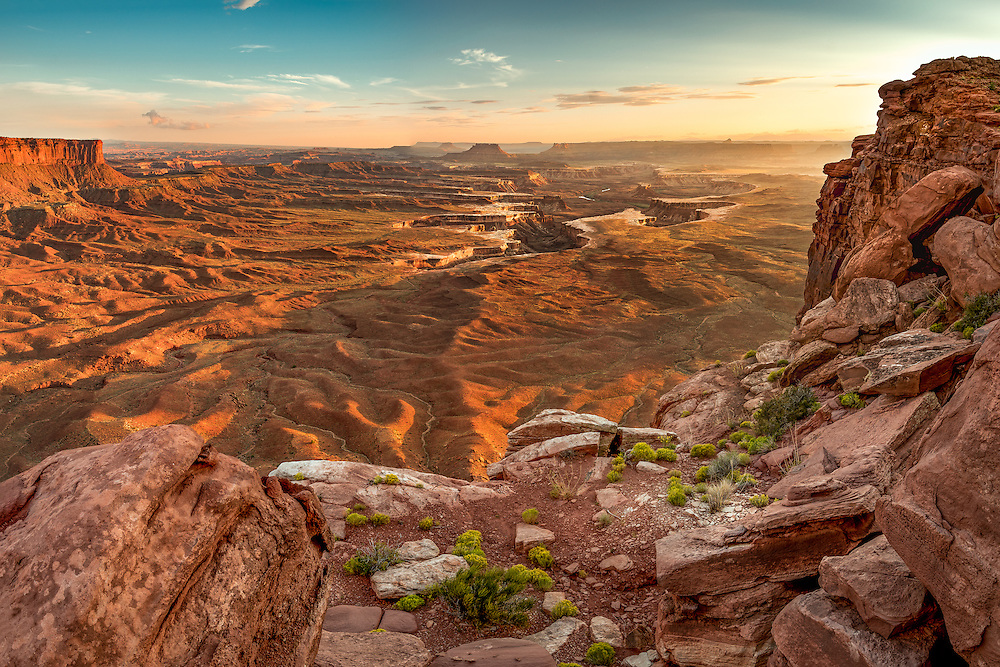 From a high vista, the Green River snakes through the canyon below as the setting sun highlights the rippled landscape in gold.  Taken within the Island in the Sky district of Canyonlands National Park, Utah.