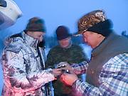 Wodka Ritual fuer eine erfolgreiche Jagd am fruehen Morgen in der sibirischen Taiga - ungefaehr 150 Kilometer entfernt von der sibirischen Stadt Jakutsk . Jakutsk hat 236.000 Einwohner (2005) und ist Hauptstadt der Teilrepublik Sacha (auch Jakutien genannt) im Foederationskreis Russisch-Fernost und liegt am Fluss Lena. Jakutsk ist im Winter eine der kaeltesten Grossstaedte weltweit mit bis zu durchschnittlichen Wintertemperaturen von -40.9 Grad Celsius.<br /> <br /> Vodka ritual for a successful hunting during an early morning in the Siberian Taiga about 150 km from the city of Yakutsk. Yakutsk is a city in the Russian Far East, located about 4 degrees (450 km) below the Arctic Circle. It is the capital of the Sakha (Yakutia) Republic (formerly the Yakut Autonomous Soviet Socialist Republic), Russia and a major port on the Lena River. Yakutsk is one of the coldest cities on earth, with winter temperatures averaging -40.9 degrees Celsius.