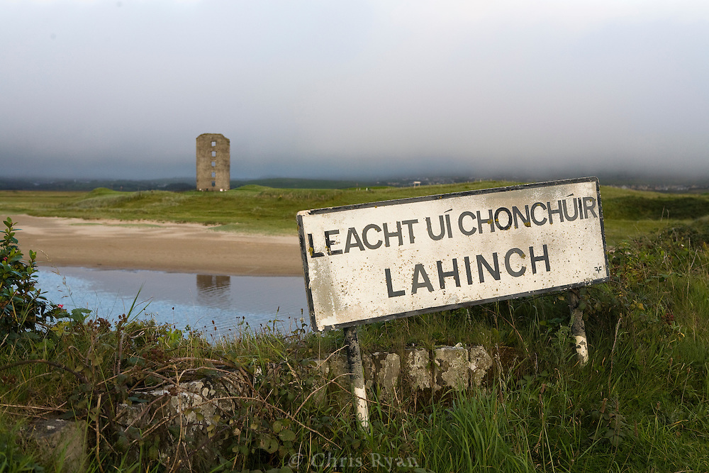 Lahinch town sign in Gaelic and the remains of Dough Castle, Lahinch, Ireland