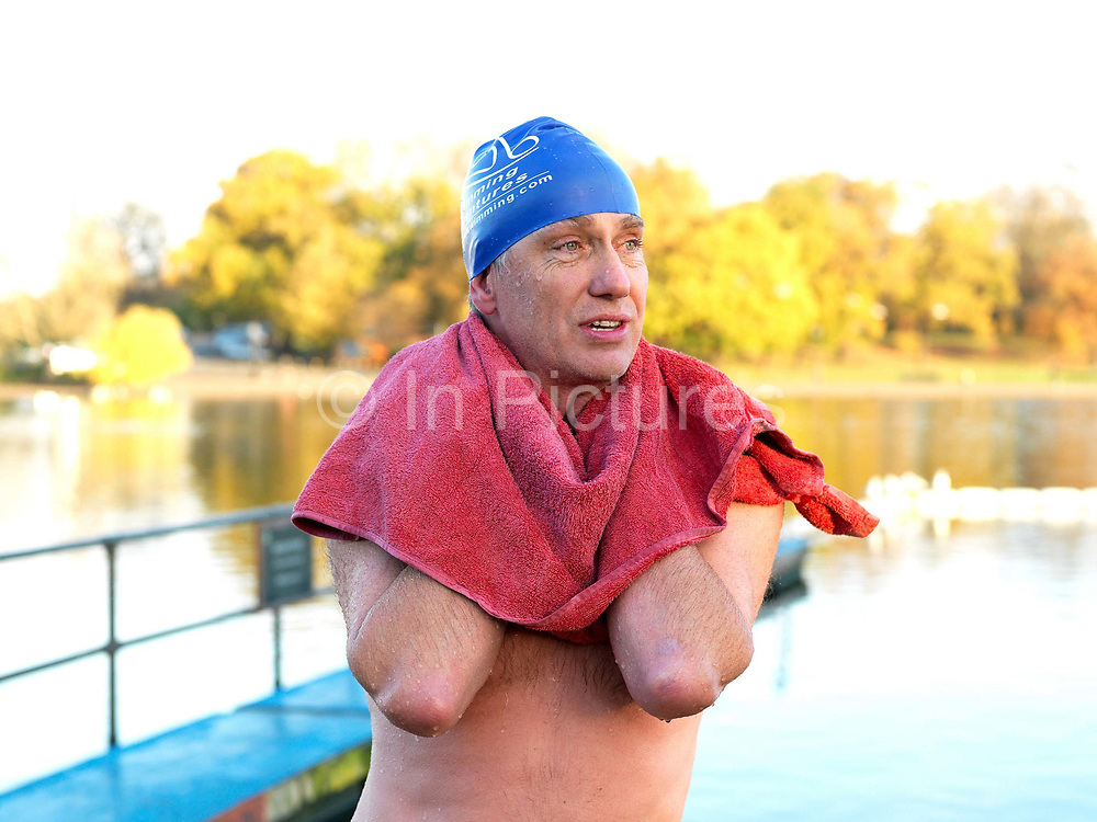 A member of the Serpentine Swimming Club dries off with a pink towel after a Saturday morning swimming race, Hyde Park, London, UK. The Serpentine Lake is situated in Hyde Park, London's largest central open space. The Serpentine Swimming Club was formed in 1864 'to promote the healthful habit of bathing in open water throughout the year'.  Its headquarters were beneath an old elm tree on the south side of the lake, a wooden bench for clothing being the only facility.  At this time London was undergoing rapid expansion and Hyde Park was now in the centre of a densely populated built up area and provided a place of relaxation to its urbanised masses. Now, the club has its own (somewhat spartan) changing facilities and members are  permitted by the Royal Parks to swim in the lake any morning before 09:30.  They race every Saturday morning throughout the year, regardless of the weather