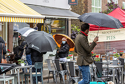 Licensed to London News Pictures. 16/05/2021. London, UK. People waiting for an outside table at a restaurant in Wimbledon Village, South West London make the most of the bad weather today as miserable May continues with grey skies and more rain with temperatures down to 14c. Weather forecasters predict yet more showers for the rest of the weekend and into next week as the bad weather continues. Photo credit: Alex Lentati/LNP
