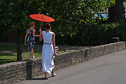 A mother and daughter walk along Richmond riverside shaded by a bright orange umbrella as record temperatures soar across England on the 25th July 2019 in Richmond in the United Kingdom. The Met Office has estimated that parts of England could reach a record-breaking 39C this afternoon.