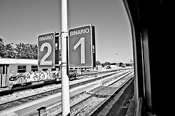 binari visti dal finestrino dello scompartimento. Reportage che analizza le situazioni che si incontrano durante un viaggio lungo le linee ferroviarie delle Ferrovie Sud Est nel Salento