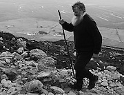 A pilgrim uses a walking stick as support through the heavy scree on the mountain.