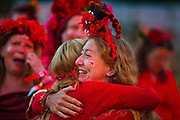 Glastonbury Festival, 2015.<br /> Women from a festival choir, dressed in red, smiling together and hugging, launching the start of the Glastonbury Festival