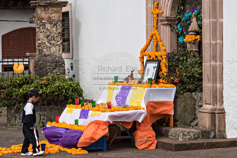 A young Mexican boy views a Day of the Dead altar decorated with marigolds outside the Templo de Nuestra Señora del Sagrario church in Santa Clara del Cobre, Michoacan, Mexico.