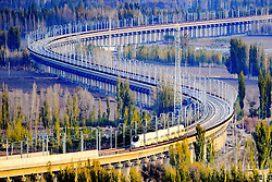 """File photo taken on Nov. 3, 2015 shows a bullet train running through a bridge on the Lanzhou-Xinjiang high-speed railway, northwest China's Xinjiang Uygur Autonomous Region. """"Building more high-speed railways"""" has been a hot topic at the annual sessions of China's provincial legislatures and political advisory bodies intensively held in January. China has the world's largest high-speed rail network, with the total operating length reaching 19,000 km by the end of 2015, about 60 percent of the world's total. The expanding high-speed rail network is offering unprecedented convenience and comfort to travelers, and boosting local development as well. Chinese companies have developed world-leading capabilities in building high-speed railways in extreme natural conditions. High-speed railway routes across China have been designed to suit its varying climate and geographical conditions. The Harbin-Dalian high-speed railway travels through areas where the temperature drops to as low as 40 degree Celsius below zero in winter, the Lanzhou-Xinjiang railway passes through the savage Gobi Desert and the Hainan Island railway can withstand a battering from typhoons. The China Railway Corp. plans to spend another 800 billion yuan (around 120 billion U.S. dollars) in 2016, especially in less-developed central and western regions. EXPA Pictures © 2016, PhotoCredit: EXPA/ Photoshot/ Cai Zengle<br /><br />*****ATTENTION - for AUT, SLO, CRO, SRB, BIH, MAZ only*****"""