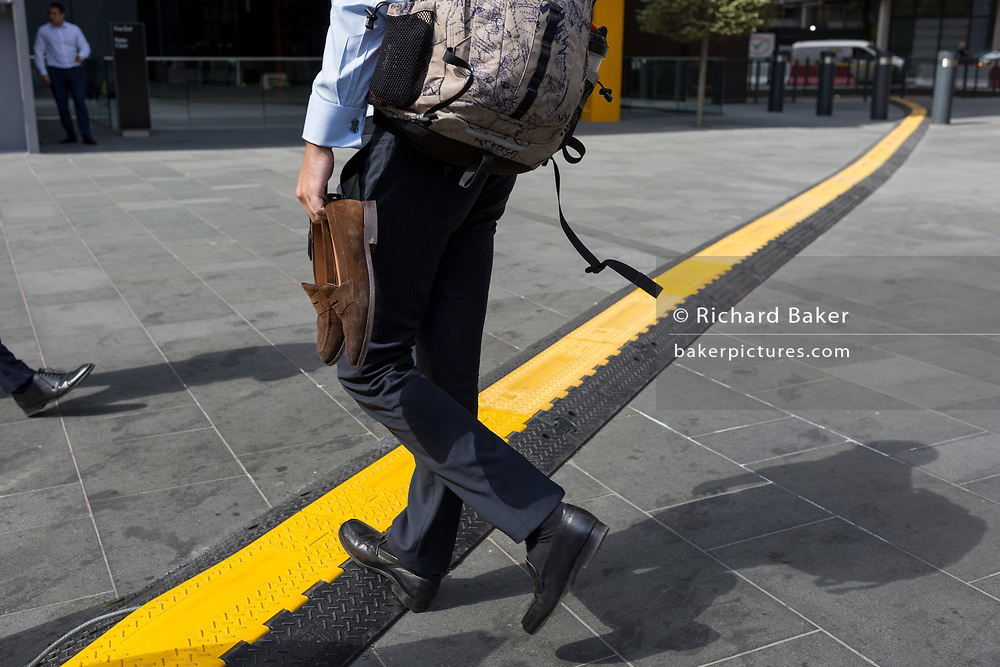 A man carrying a spare pair of shoes crosses a yellow line that covers hazardous electrical cabling at Leadenhall in the City of London, (aka The Square Mile) the capital's financial district, on 2nd September 2019, in London, England.