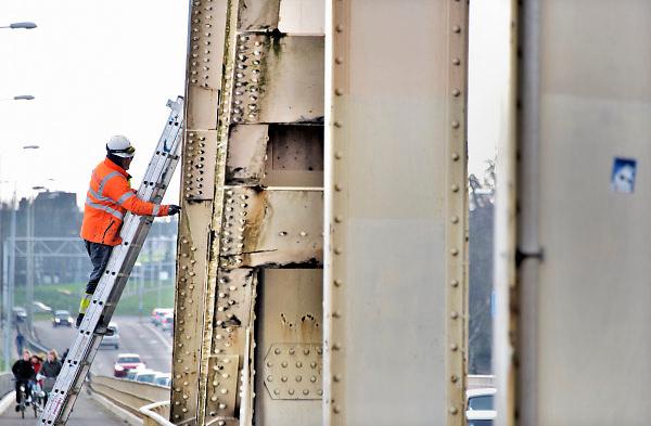 Nederland, Nijmegen, 5-2-2018Eerste verfstreken op de Waalbrug. Vier vlakken grijs worden door een gespecialiseerd schildersbedrijf aangebracht om een definitieve kleurkeuze te kunnen maken. De brug wordt de komene maanden grondig gerenoveerd en opgeknapt. Het onderhoud is hard nodig want op veel plaatsen zijn dikke plakken roest onder meer van opspattend strooizout gevormd .  De tweecomponenten verf droogt tot -5 graden .Foto: Flip Franssen