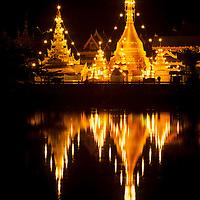 Wat Chong Kham temple lights are reflected in still reservoir, Mae Hong Son, Thailand