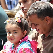 A man plays with his daughter as he waits for Friday prayers to begin in Cairo's Tahrir Square.