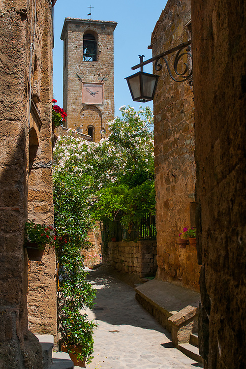 """A view of the streets of the village of Civita di Bagnoregio.<br /> Civita di Bagnoregio is a town in the Province of Viterbo in central Italy, a suburb of the comune of Bagnoregio, 1 kilometre (0.6 mi) east from it. It is about 120 kilometres (75 mi) north of Rome. Civita was founded by Etruscans more than 2,500 years ago. Bagnoregio continues as a small but prosperous town, while Civita became known in Italian as La città che muore (""""The Dying Town""""). Civita has only recently been experiencing a tourist revival. The population today varies from about 7 people in winter to more than 100 in summer.The town was placed on the World Monuments Fund's 2006 Watch List of the 100 Most Endangered Sites, because of threats it faces from erosion and unregulated tourism."""
