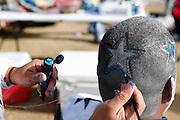Melinda Balderas  paints Juan Rodriguez's hair in parking lot 4 before the Cowboys game against the Pittsburgh Steelers at Cowboys Stadium in Arlington, Texas, on December 16, 2012.  (Stan Olszewski/The Dallas Morning News)
