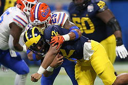 Michigan Wolverines running back Chris Evans #12 is tackled by Florida Gators defensive back Chauncey Gardner-Johnson #23 during the Chick-fil-A Peach Bowl, Saturday, December 29, 2018, in Atlanta. (Jason Parkhurst via Abell Images for Chick-fil-A Peach Bowl)