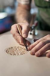 Lute manufacturer carving out ornament out of wood